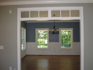 Custom room with open door header and wall trim