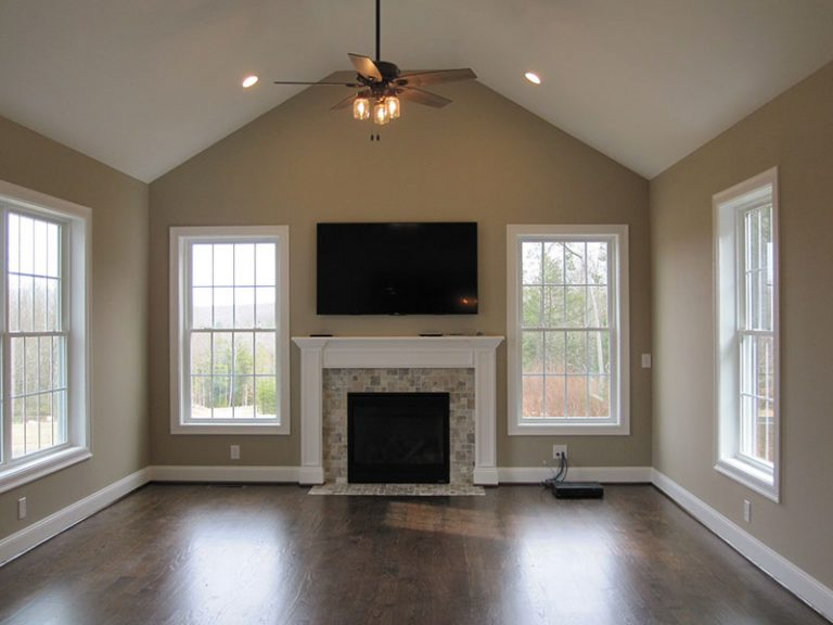 View of room with TV above fireplace and windows on either side