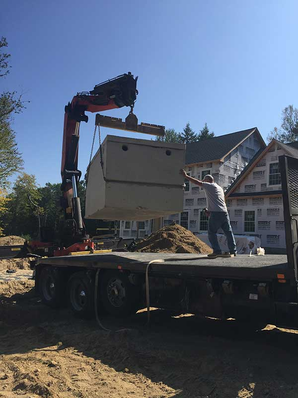 Unloading tank from truck for septic installation